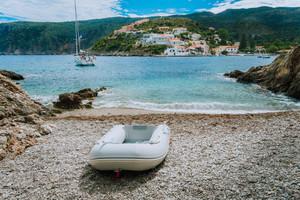 A dinghy on small hidden beach in Assos village. White yacht in Assos bay. Kefalonia Greece