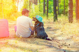 A man is sitting with a dog on a path in the forest. The dog is wearing a sun hat