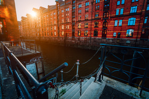 A red brick multi-storey houses of Speicherstadt Hamburg. Famous landmark of old red brick buildings in golden sunset light. Scenic evening view with canal handrail in foreground