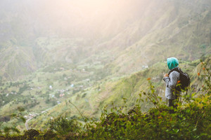 A Tourist with backpack admire the rural landscape with mountain ridge in Xo-Xo Valley. Santo Antao Island. Cape Verde