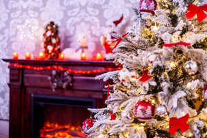 A traditional fireplace with lots of candles and christmas tree. Christmas decoration.