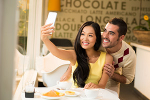 A young attractive couple photographing at a coffee shop on the foreground