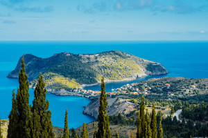 Above view to Assos village and beautiful blue sea. Cypress trees stands out in foreground. Kefalonia island, Greece