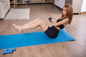 Abs workout with dumbbels by beautiful young woman. No pain no gain