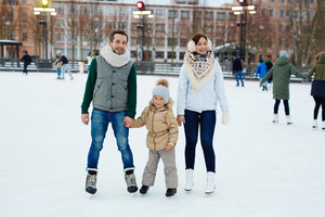 Active couple and their daughter skating on ice-rink in urban environment