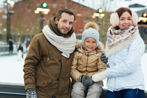 Active family of three spending weekend on skating-rink