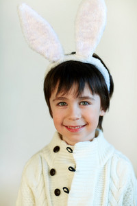 Adorable boy with bunny ears looking at camera