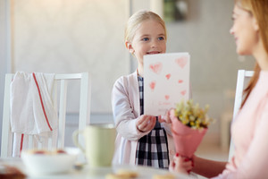 Adorable child giving her mother handmade card as gift
