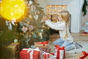 Adorable girl preparing firtree for xmas day