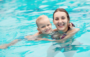 Adorable mom and kid keeping fit and healthy in water