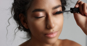 Adorable teenage Middle Eastern girl with great skin applying mascara to her long lashes on white background