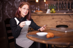 Adult business lady using a smartphone while holding a cup of coffee. Relaxing in a vintage coffee shop