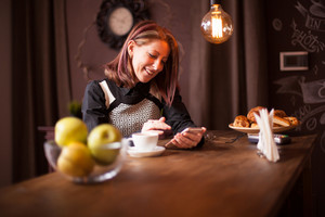 Adult business woman laughing while holding her phone. Relaxing in coffee shop