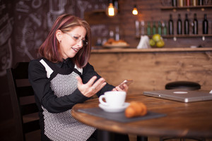 Adult businesswoman amazed while using her phone next to french croissant. Beautiful vintage pub