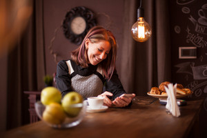 Adult businesswoman laughing while looking at her phone. Recreation in vintage coffee shop