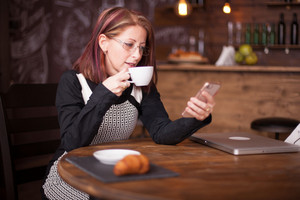 Adult businesswoman reading emails from her phone while having a cup of coffe in a restaurant