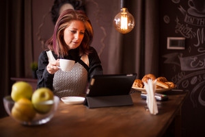 Adult businesswoman searching on her tablet in a vintage coffee shop. Next to a bowl of green apples