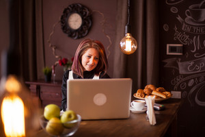 Adult entrepreneur woman smiling at her laptop next to a bowl of green appels.