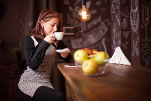 Adult woman enjoys her cup of coffe at bar counter. Woman relaxing in vintage coffee shop