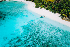Aerial drone above view of paradise isolated beach. Lonely tourist boat in turquoise shallow lagoon ocean water surrounded by coconut trees
