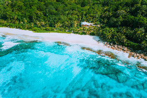 Aerial drone photo of great tropical dream beach Anse Bazarca, Mahe island, Seychelles. White powdery sand, azure water, lush vegetation, granite rocks