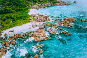 Aerial drone photo of group of rocks on tropical hidden secret beach Marron at La Digue island, Seychelles. White sand beach with turquoise ocean water and orange granite rocks