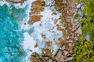 Aerial drone photo of Seychelles tropical beach Anse Cocos at La Digue Island. White rolling waves splash granite coastal rocks. Travel and vacation concept