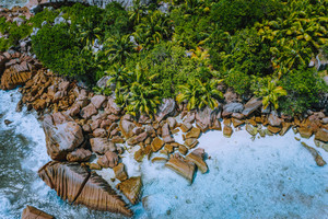 Aerial drone photo of stony boulders of beautiful Anse Cocos beach at La Digue, Seychelles