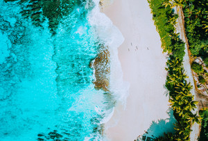 Aerial photo of amazing paradise tropical beach Anse Bazarca at Mahe island, Seychelles. White sand, turquoise water lagoon, palm trees and teal granite rocks