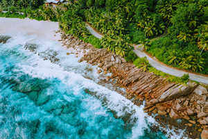 Aerial photo of coastal road along paradise tropical rocky beach at Seychelles. Summer vacation, travel and lifestyle concept