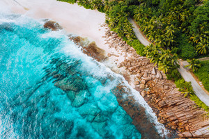 Aerial photo of ocean waves hitting rocky coastline of beautiful paradise dream tropical beach at Seychelles. Summer vacation, travel and lifestyle concept