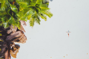 Aerial photo of young woman laying on exotic tropical beach with white sand. Girl sunbathing and relaxing near rockstone and palm trees. Concept of travel vacation holidays in paradise