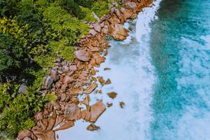 Aerial top view of ocean waves hitting granite rocks on the anse cocos beach in La Digue, Seychelles