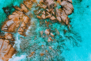 Aerial top view of ocean waves hitting granite rocks on the beach in La Digue, Seychelles