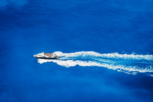 Aerial top view of tourist speed boat sailing in the deep blue sea