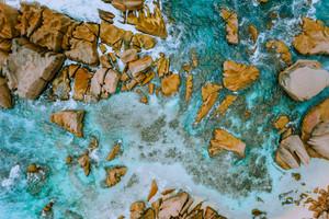 Aerial top view of tropical coastline. Bizarre granite rocks boulders, turquoise azure water. Amazing shore seascape Seychelles La Digue Island