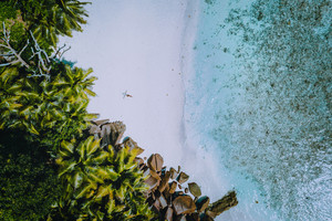 Aerial view of a young woman with on the tropical paradise beach. Crystal clear water, summer luxury exotic romantic vacation, honeymoon