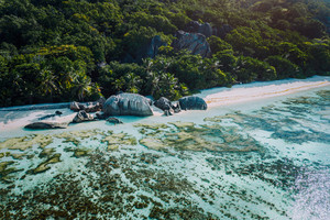 Aerial view of bay with shallow water on early morning of unique Anse Source D'Argent tropical beach, La Digue Seychelles. Luxury exotic travel concept