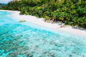 Aerial view of boat moored at uninhabitable island with tropical beautiful azure blue lagoon, Seychelles