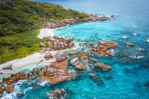 Aerial view of Seychelles tropical Marron beach at La Digue island. White sand beach with turquoise ocean water and quaint granite rocks. tropical paradise