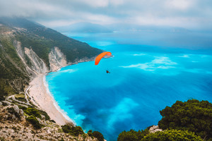 Aerial view of the paraglider flying over gorgeous Myrtos beach. Amazing water colors and beautiful coastline on kefalonia island, Greece