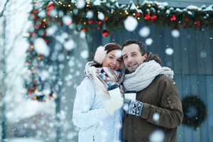 Affectionate man and woman with hot drinks looking at camera in snowfall