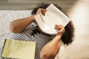 African american college student doing homework in bed at home. Black woman studying chemistry formulas, having problems to memorize notes on exercise book.