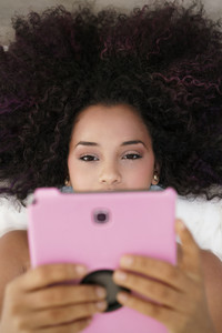 African american college student doing schoolwork on bed at home, young black woman reading on website for school test on ipad digital tablet