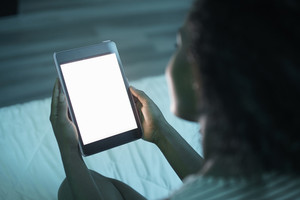 African american woman at home with tablet. Girl watching empty screen of device at night. Over the shoulder shot of blank monitor for mock-up.