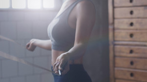 african american woman makes a jump rope routine in sunny loft for healthy life side view body closeup. Soft focusocus on hand
