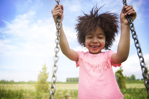 African girl loves swinging at the playground
