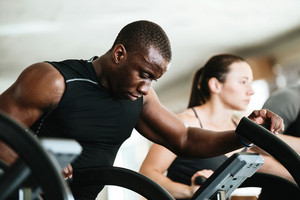 Afro american sportsman exercising on a treadmill at the gym with people on a background