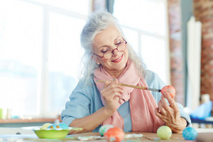 Aged female painting Easter eggs for holiday