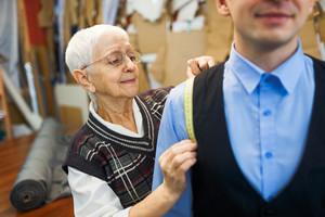 Aged female taking measures of customer waistcoat